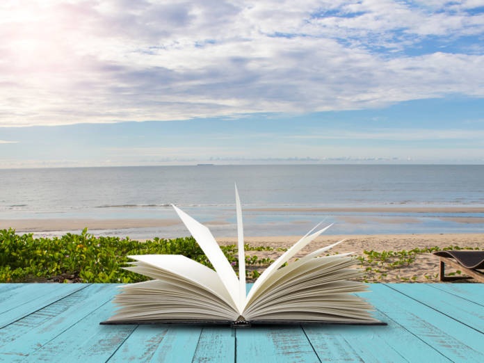 Open book on blue wooden plank with sea beach background