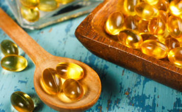 Cod Liver Oil Capsules on wooden spoon