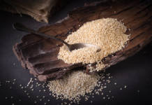 Dried quinoa grains, on a wood and dark background.