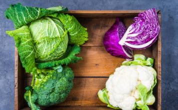 Cabbages in wood rustic box, savoy green cabbage, broccoli, cauliflower, red cabbage top view.