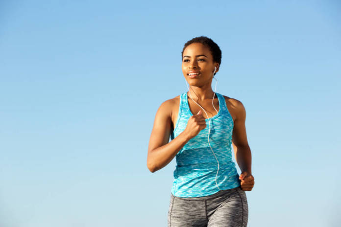 Portrait of happy young fitness woman running with earphones