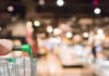 woman hand hold supermarket shopping cart with Abstract grocery store shelves blurred defocused background with bokeh light