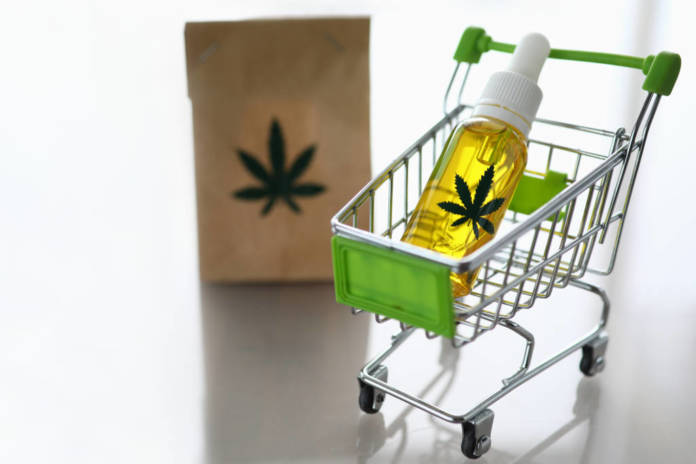 Cart from the supermarket with bottle of hemp oil on gray background with reflection