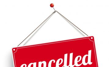 Red sign with the text cancelled, on the wooden board.