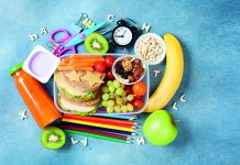 Back to school concept. Nutritional lunch box and colorful stationery on blue table top view.