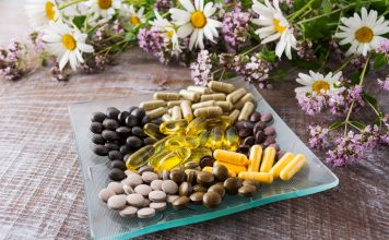 Ayurvedic herbal pills on the glass plate with wild chamomile and tansy flowers. Healthy life concept