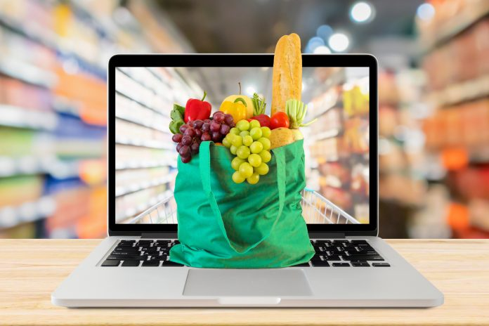 supermarket aisle blurred background with laptop computer and green shopping bag on wood table grocery online concept what's selling