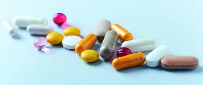 Multicolor vitamins and supplements on bright paper background. Concept for a healthy dietary supplementation. Close up.