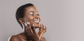 Face lifting concept. Happy black woman with closed eyes touching soft smooth skin on her cheeks over grey background, panorama