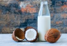 Whole coconuts and coconut products as milk and powder. White stone background.