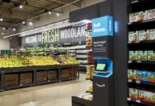 """Start ID: Image is centered on an Alexa station, a screen below a sign saying """"Ask Alexa. Need help? Try saying: [text illegible due to distance]"""" To the right of the stand is a shelf of snack foods. To the left, farther away than the Alexa stand and the snack shelf, is the produce section. On the wall it says """"Welcome to FRESH Woodland"""". End ID."""