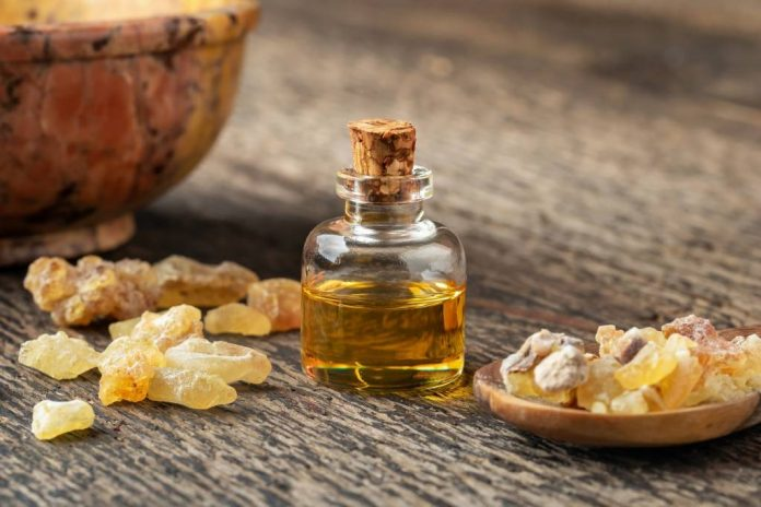 Boswellia oil in a bottle and pieces of resin on a wood table
