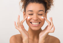 Skin care. Laughing girl applying moisturizing cream on her face over white background