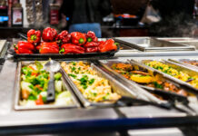 Buffet bar and trays with roasted salad vegetables, red bell peppers and meat dishes