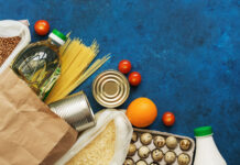 Food Home Delivery. Oil in a bottle, pasta, canned food, cereals, eggs, milk, fruits and vegetables on a blue rustic background. Donation and charity. Top view, flat lay,copy space