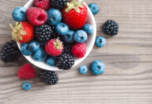 Fresh berries in a basket on rustic wooden background. Close up, top view, high resolution product. Harvest Concept