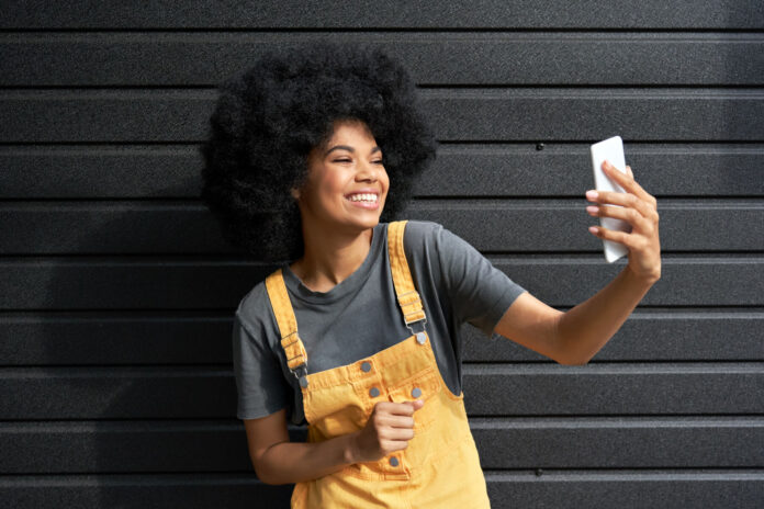 Happy African American hipster teen girl blogger with Afro hair laughing, holding phone, recording vlog, shooting social media stories or video calling in mobile app standing on black background.