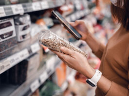 Closeup - Woman shopping in supermarket and reading product information. Costumer buying food at the market.